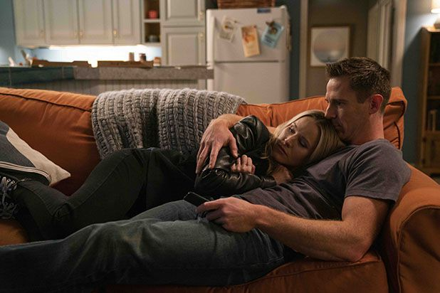 Kristen Bell as Veronica Mars and Jason Dohring as Logan cuddling on a couch.
