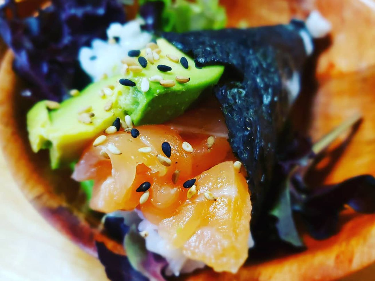 A seaweed-wrapped hand roll with rice, salmon, and avocado topped with sesame seeds