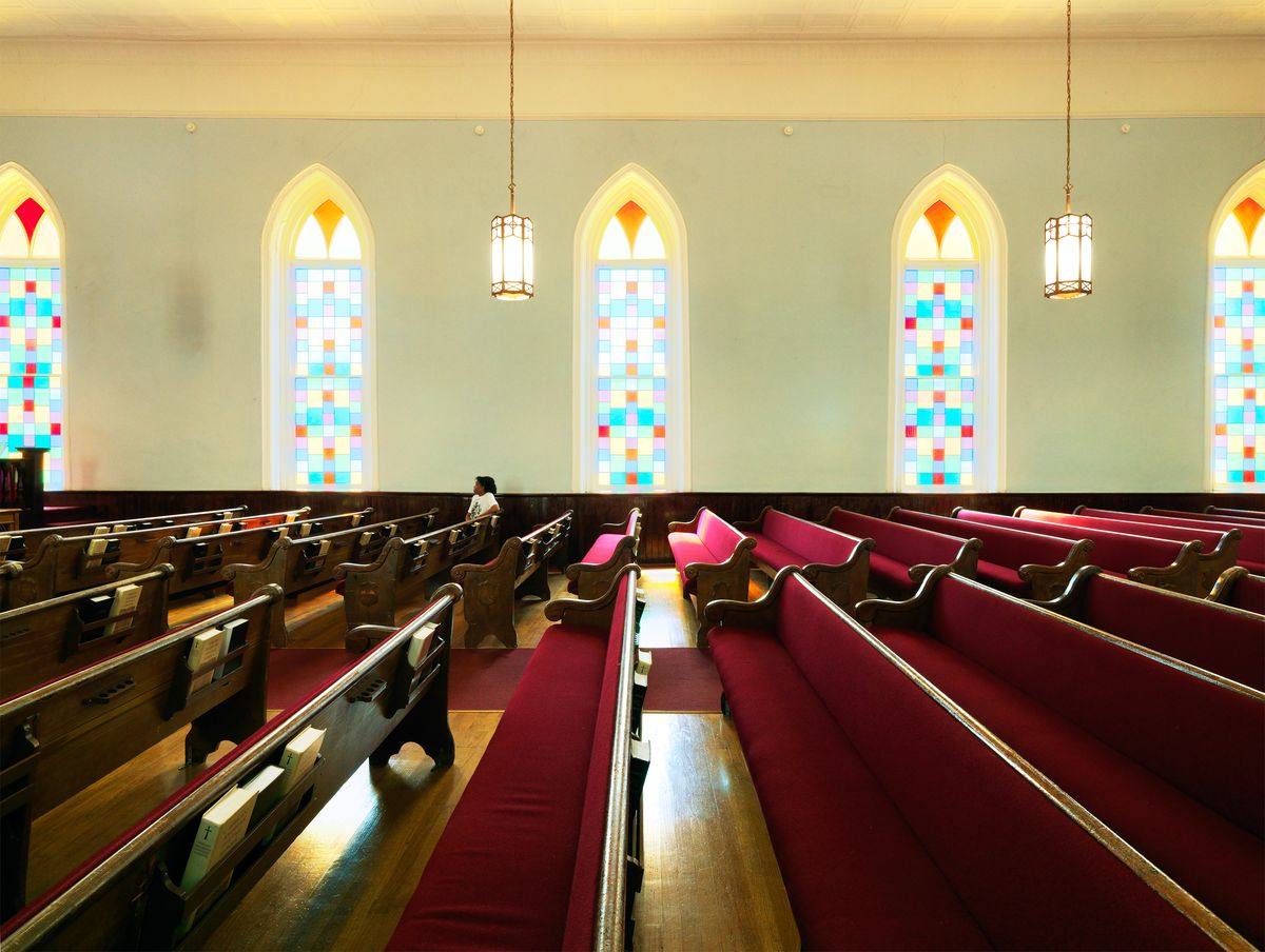 The interior of a church, with pastel stained glass windows and cushioned pews.