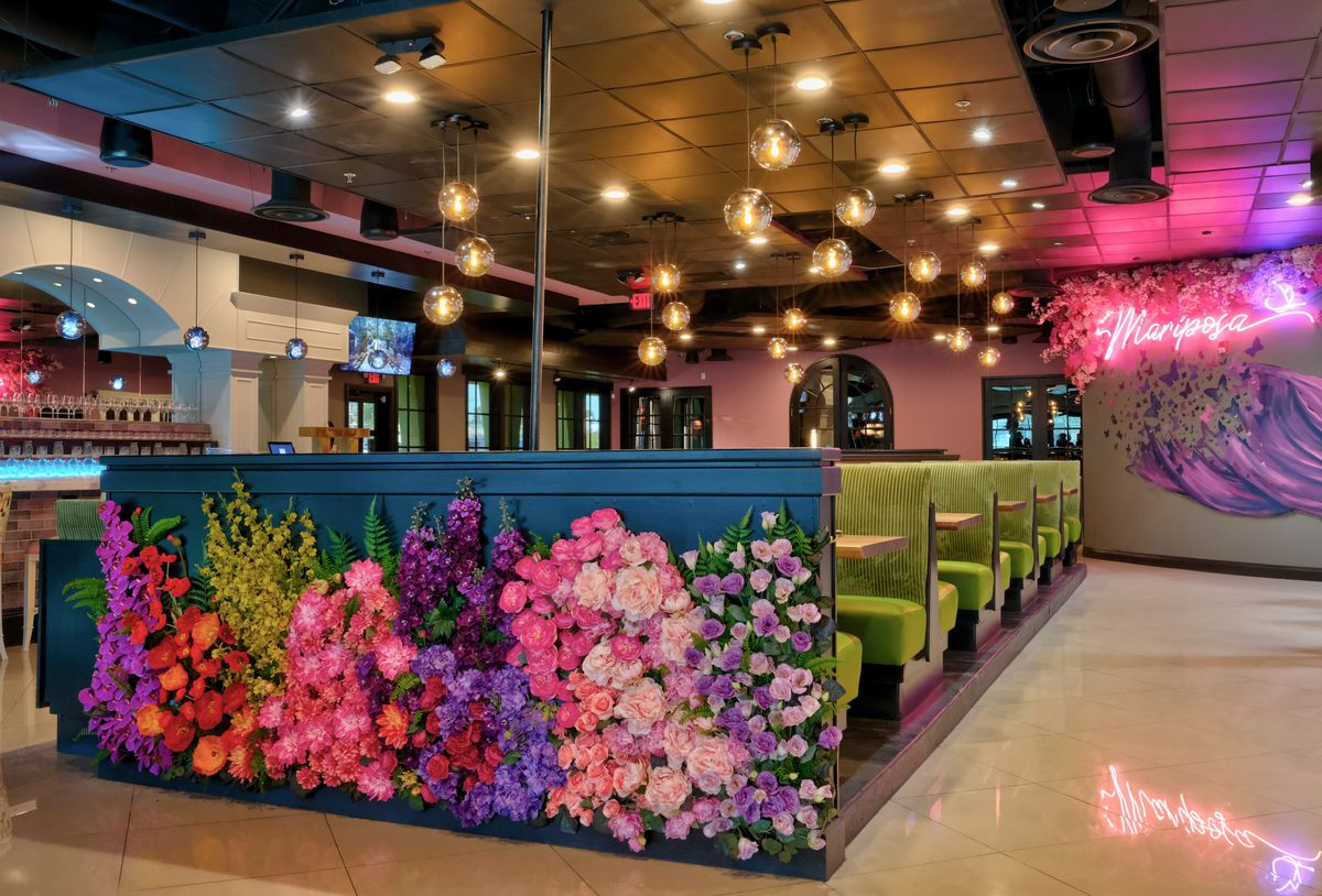 A lounge with a floral mural and green booths