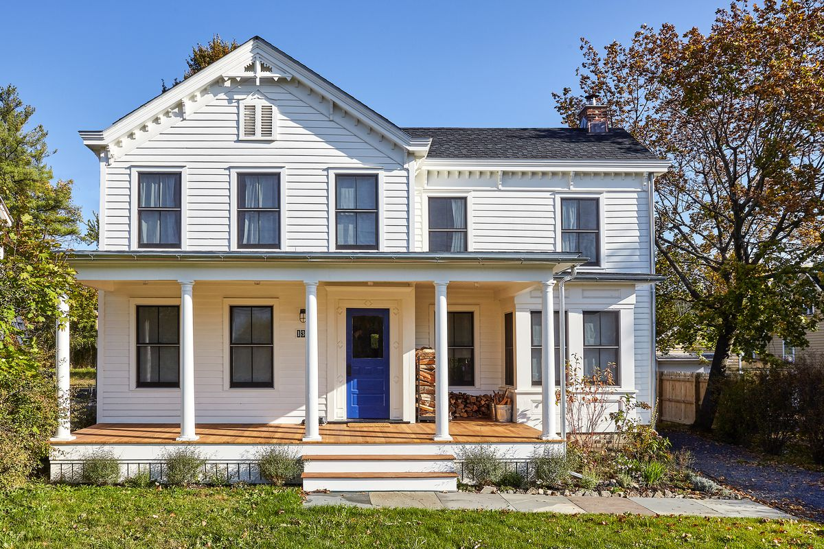 A white Victorian house with a blue front door.