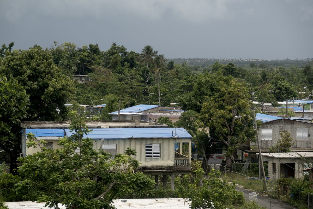 Blue tarps cover houses visible from the expressway in the Northern town of Canovanas on September 19, 2018 in Canóvanas, Puerto Rico.