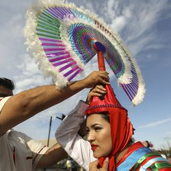Paola Sepulveda puts on an Indigenous Pueblo penachos to march in the Days of '47 Parade with the Consulate of Mexico in Salt Lake City on Friday, July 23, 2021.