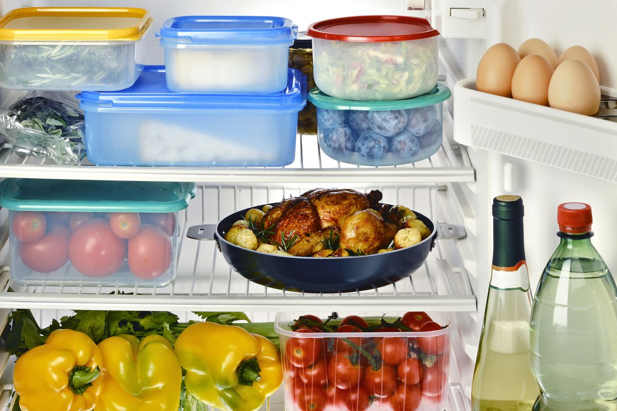 Inside a well-organized fridge with plastic storage contains, fresh vegetables, and eggs.