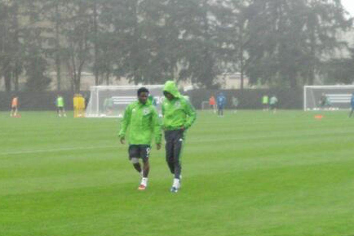 Obafemi Martins and Steve Zakuani leave practice under a heavy rain