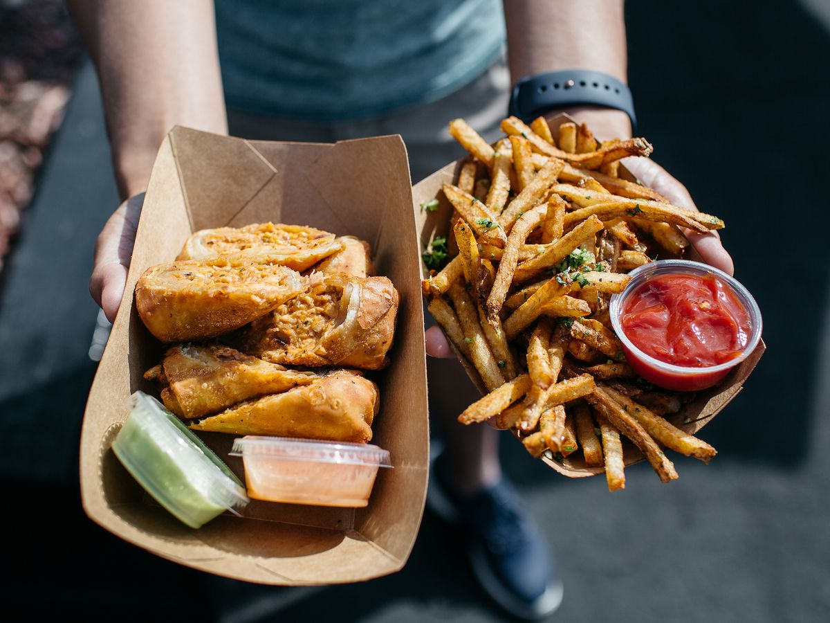 Egg rolls and cilantro garlic fries inside brown paper boats are held in someone's hands.