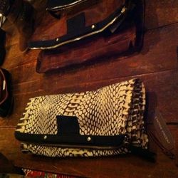 """Cynthia's favorite piece, """"the bankers clutch,"""" in the new python print that she uses throughout the collection."""