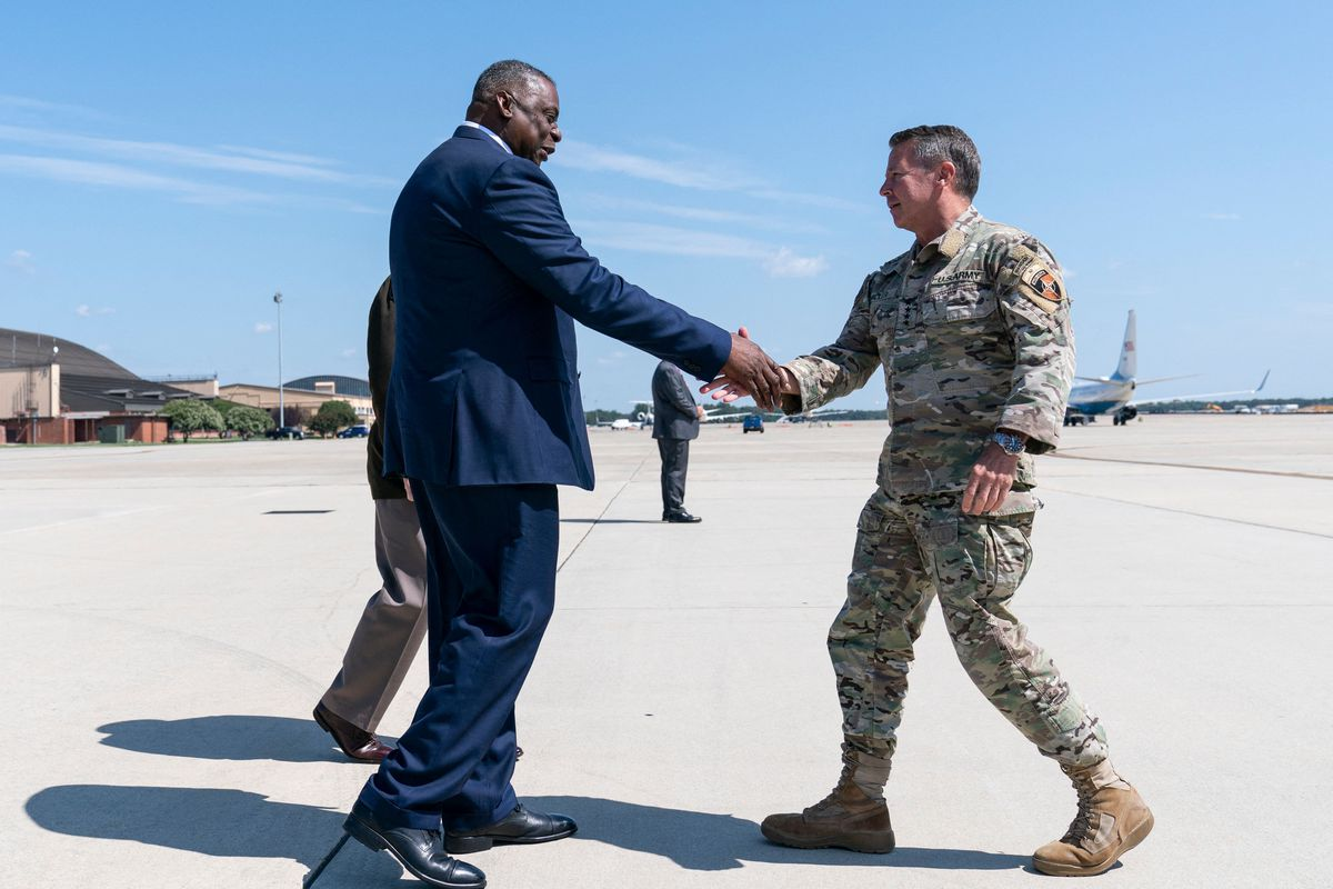The two men shake hands on a military runway, Austin, a tall Black man in a navy suit; Miller, a white man with gray hair in light-patterned Army fatigues and boots.