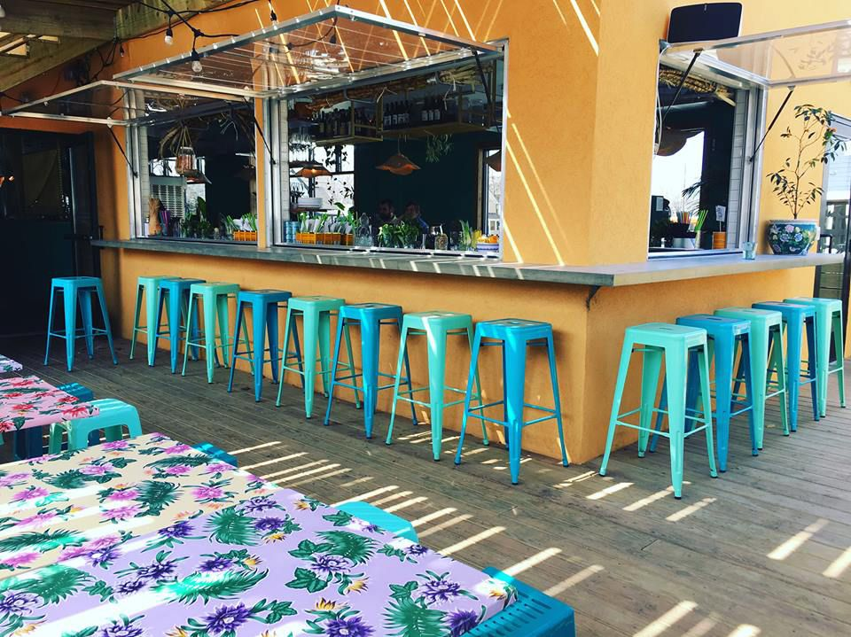 Brightly colored metal bar stools surround an open bar window