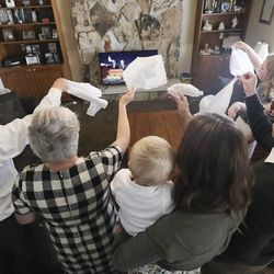 Ron and Wendy Van Tienderen, left, participate in the Hosanna Shout as they watch the Sunday morning session of the 190th Annual General Conference of The Church of Jesus Christ of Latter-day Saints with their children at their home in Millcreek on Sunday, April 5, 2020.