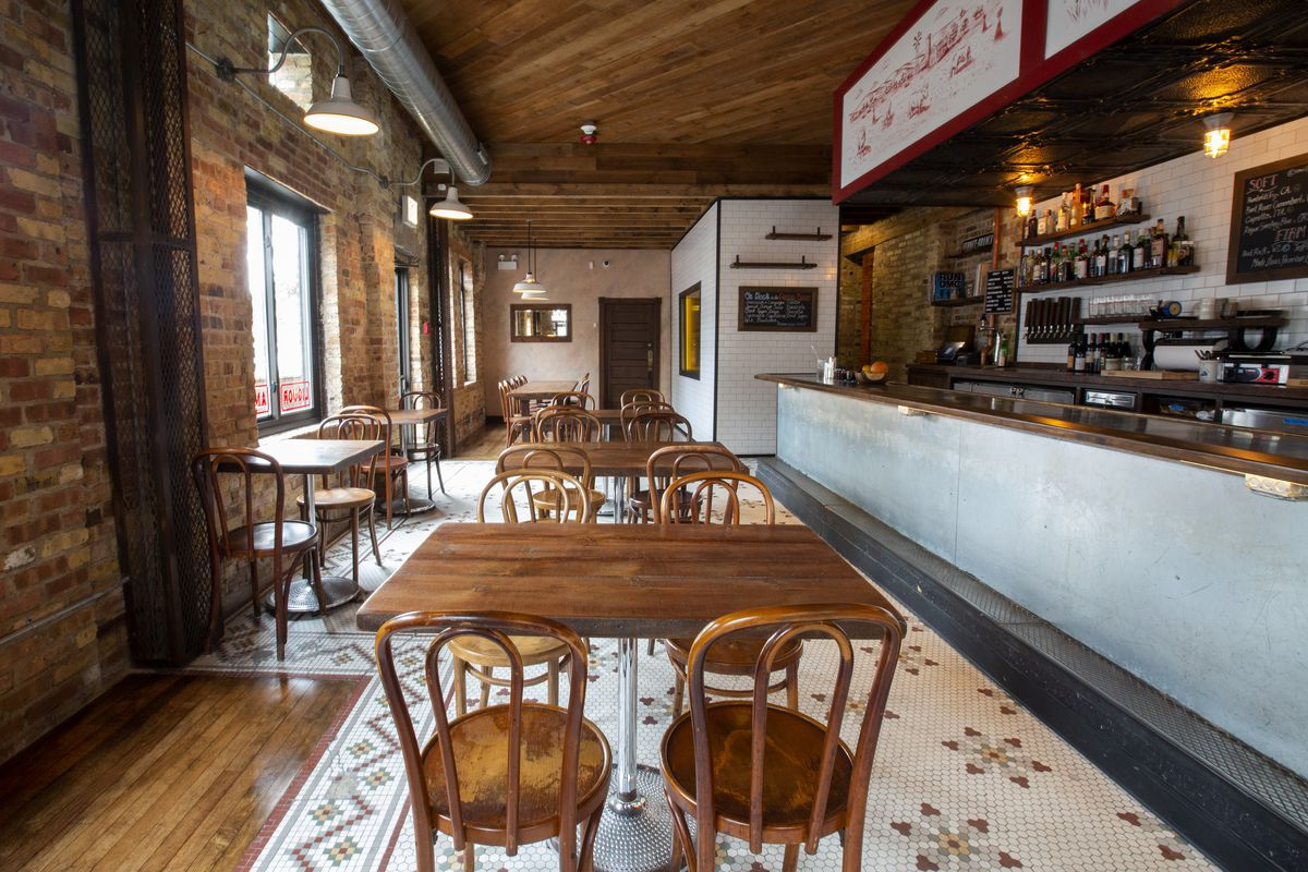 A cafe space with wooden furniture and exposed brick walls.