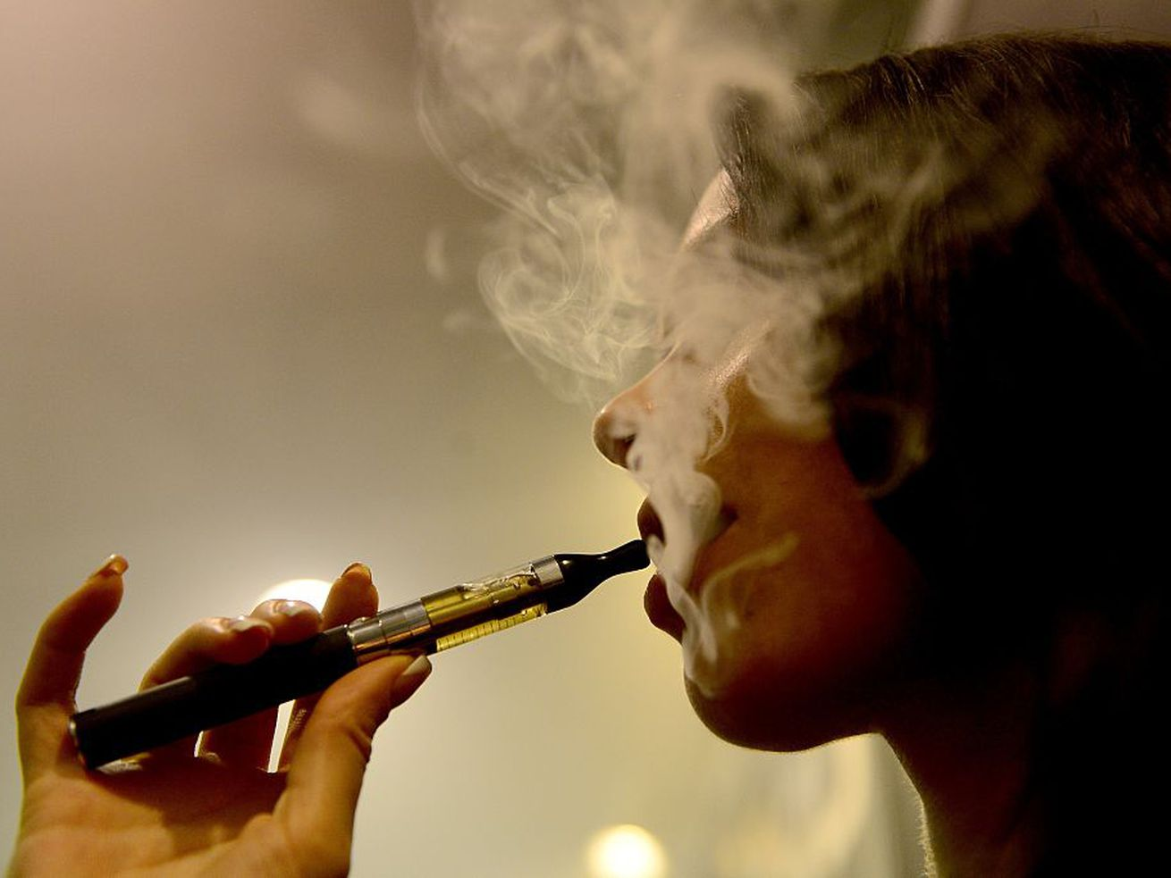 A woman vapes on an electronic cigarette.