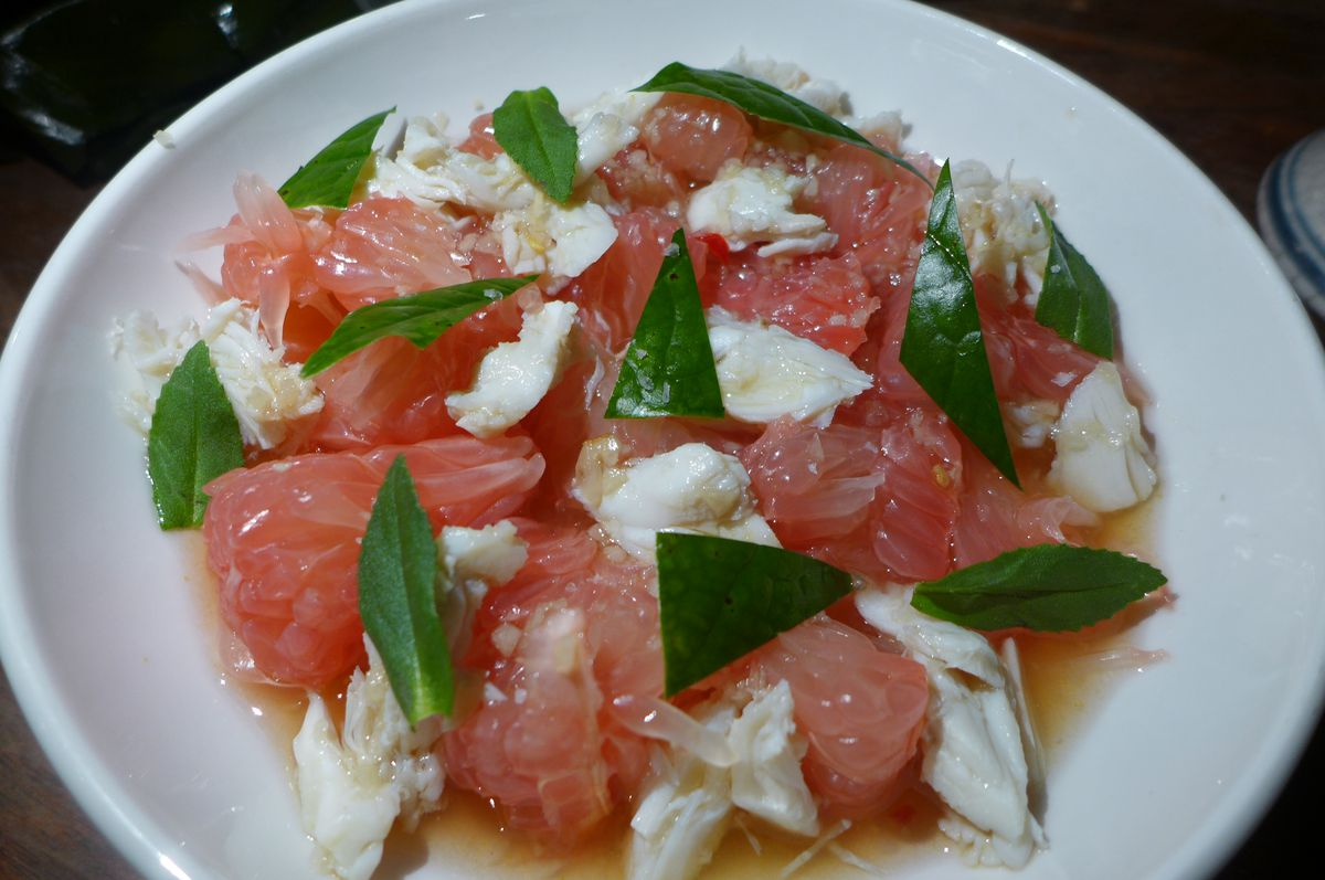 A salad arrange in a circle with pink pomelo, white crabmeat, and torn green betel leaves.