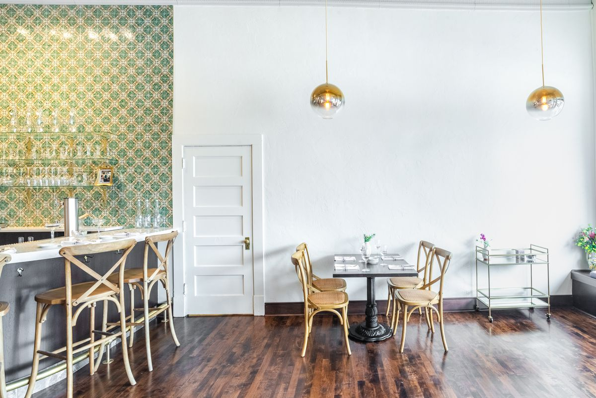 A light-filled room with a bar and small table set nearby