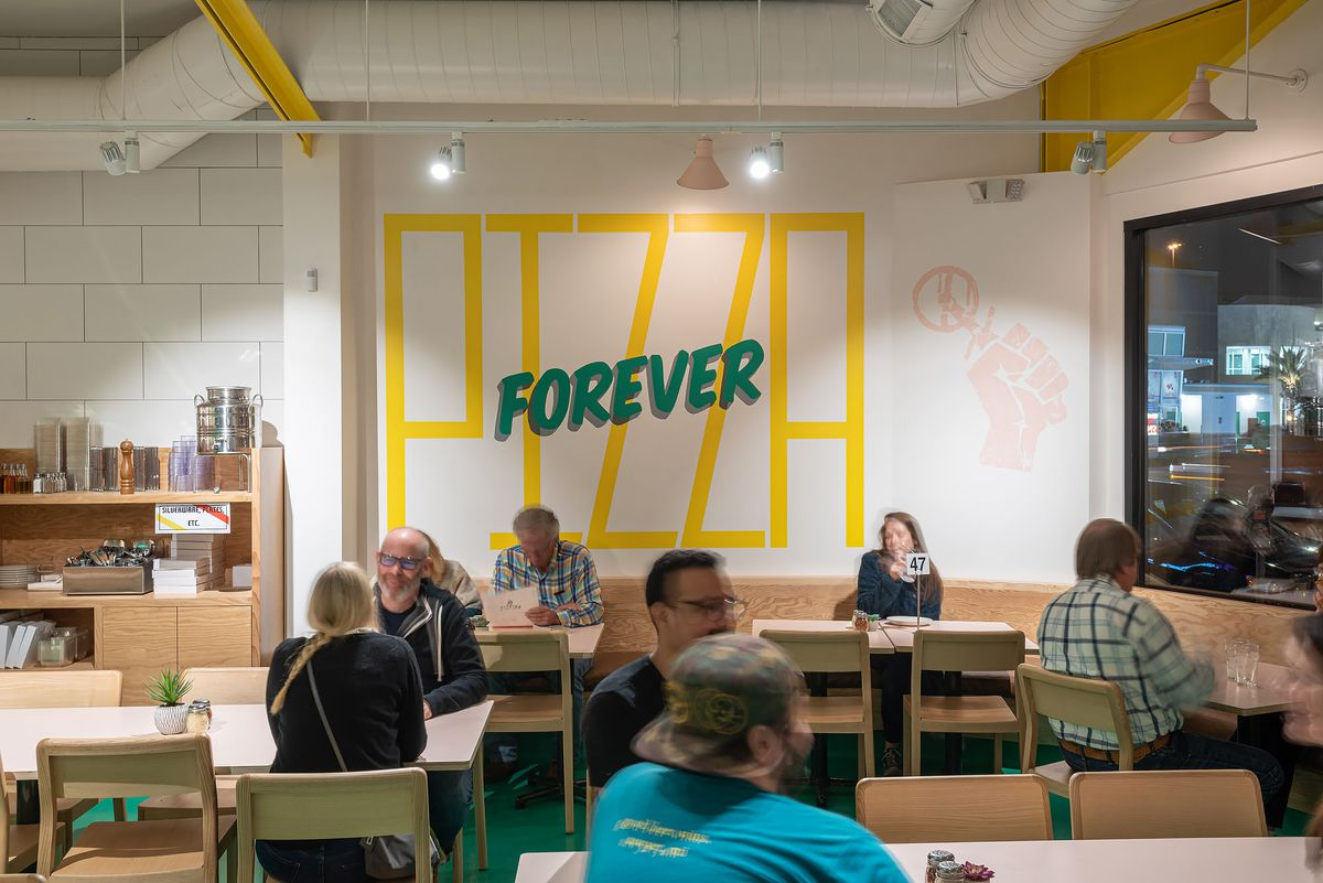 A yellow and light green painting says Pizza Forever on a wall.