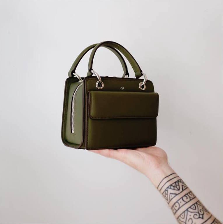 A woman with tattoos holding an olive green handbag