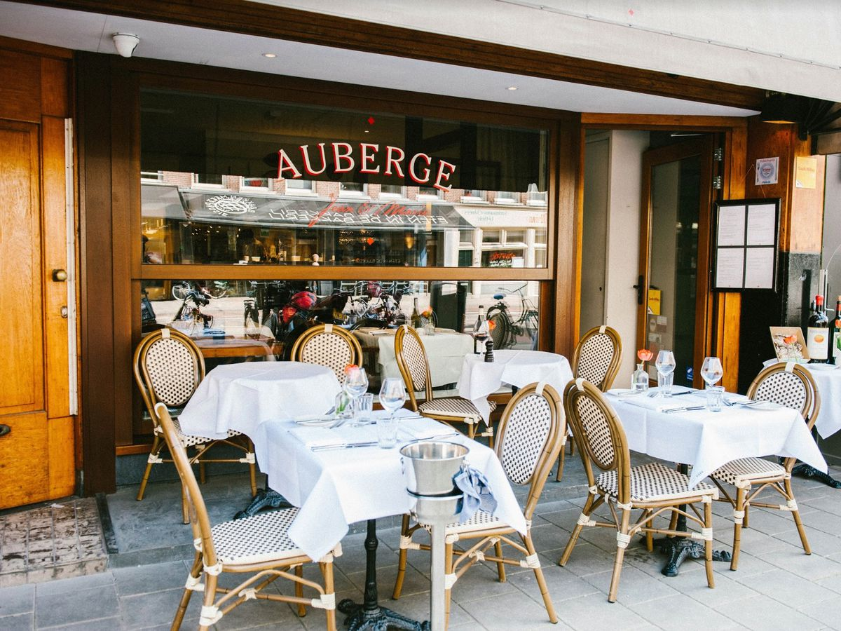 The exterior of the Auberge Jean & Marie restaurant, with the name of in large brasserie-like lettering on the window behind empty white tablecloth-covered tables and patio chairs.