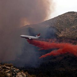 Tanker 910 makes a retardant drop on the Yarnell Hill Fire to help protect the Double Bar A Ranch near Peeples Valley, Ariz., Sunday, June 30, 2013. The fire started Friday and picked up momentum as the area experienced high temperatures, low humidity and windy conditions. It has forced the evacuation of residents in the Peeples Valley area and in the town of Yarnell. (AP Photo/The Arizona Republic, Tom Story)