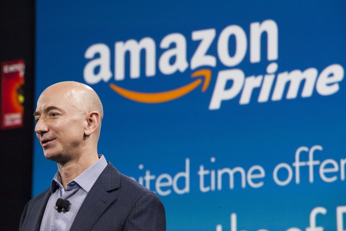 Amazon CEO Jeff Bezos stands in front of an Amazon Prime image