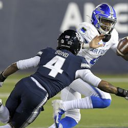 Air Force quarterback Haaziq Daniels, right, carries the ball as Utah State safety Shaq Bond defends during the first half of an NCAA college football game Thursday, Dec. 3, 2020, in Logan, Utah.