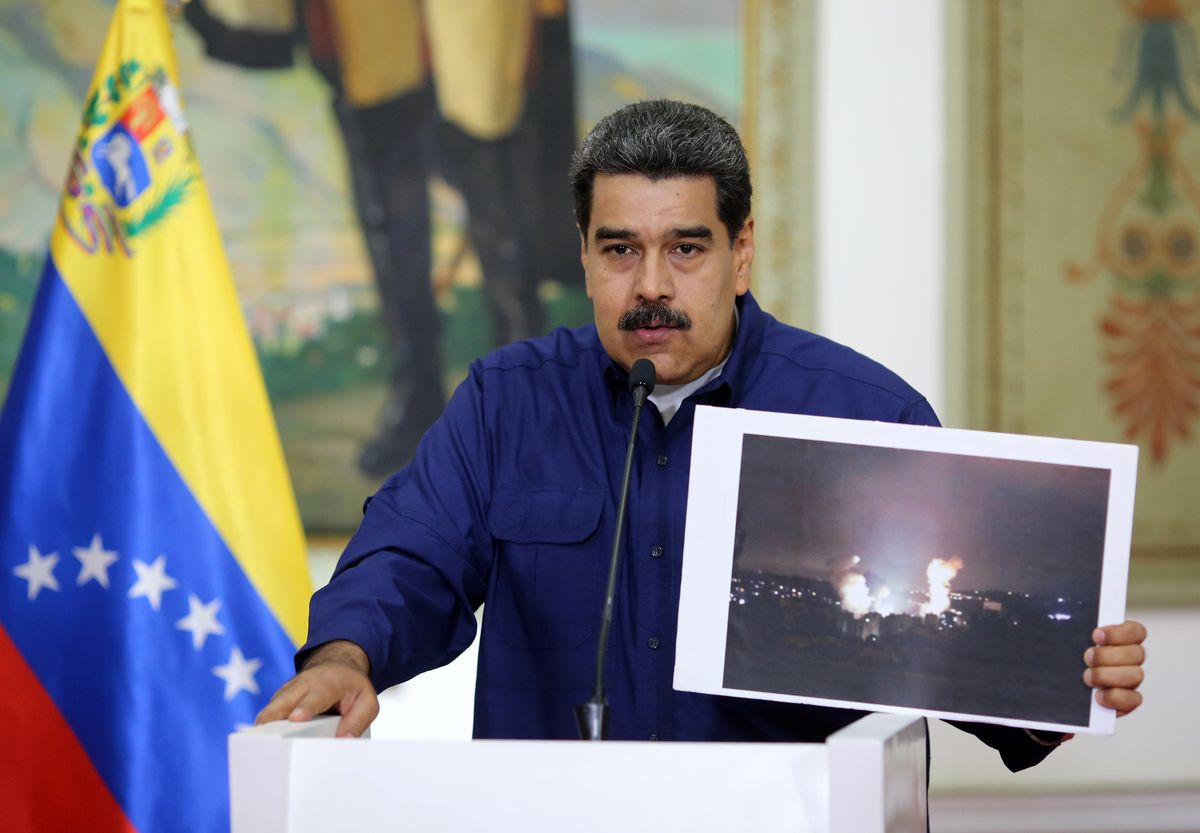 Handout picture released by the Venezuelan presidency showing Venezuelan President Nicolas Maduro showing a picture of the fire at a state owned electricity company Corpoelec power substation, during a press conference at the Miraflores Presidential Palac