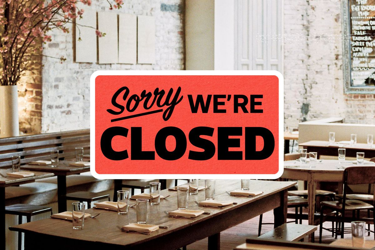 An empty restaurant with tables set with a big read sign reading Sorry, We're Closed in black letters