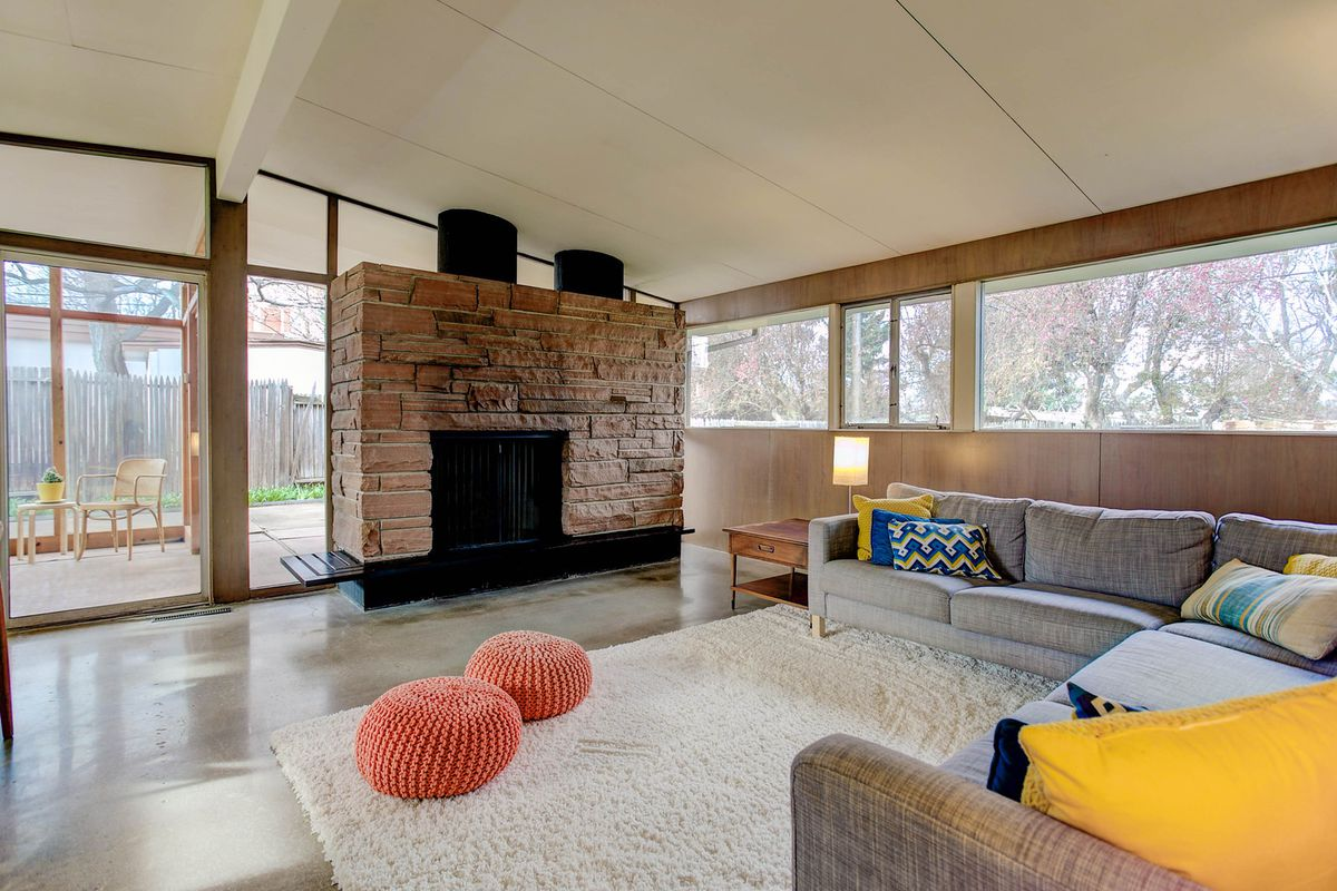 Interior shot of vaulted living room with floor-to-ceiling windows on one side and a ribbon of windows on the other, with a large stone fireplace with cylindrical flues at the center and couches facing toward it.