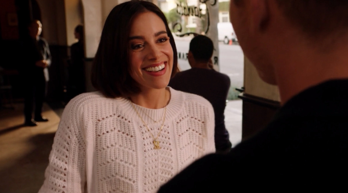 A smiling brunette woman wearing a white sweater