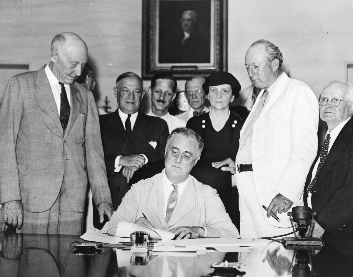 President Roosevelt signs Social Security Act, at approximately 3:30 pm EST on 14 August 1935. Standing with Roosevelt are Rep. Robert Doughton (D-NC); unknown person in shadow; Sen. Robert Wagner(D-NY); Rep. John Dingell (D-MI);