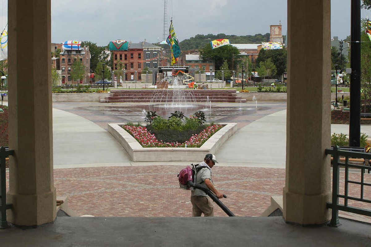 In this July 5, 2012 photo, a worker cleans the steps of the bandstand at Washington Park in the Over-the-Rhine section of Cincinnati. Three residents of a historic Cincinnati neighborhood have filed a lawsuit in federal court over a newly renovated urban