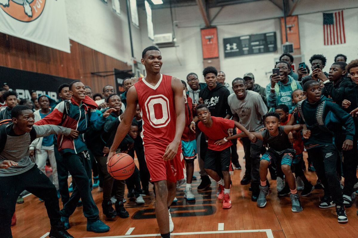 A young black man in a basketball uniform bounces a basketball while surrounded by his fellow high school students.