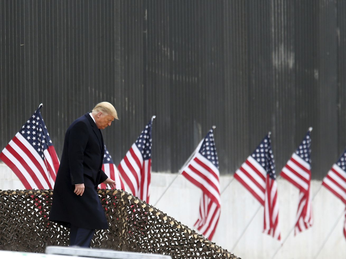 President Donald Trump walks down the steps before a speech near a section of the U.S.-Mexico border wall, Tuesday, Jan. 12, 2021, in Alamo, Texas.