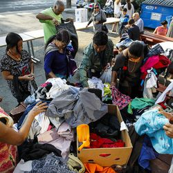 Refugees from Bhutan, Iraq, Sierra Leone, Guatemala and Peru look through clothes at the Mosaic Inter-Faith center in Salt Lake City on Thursday, Aug. 4, 2016.