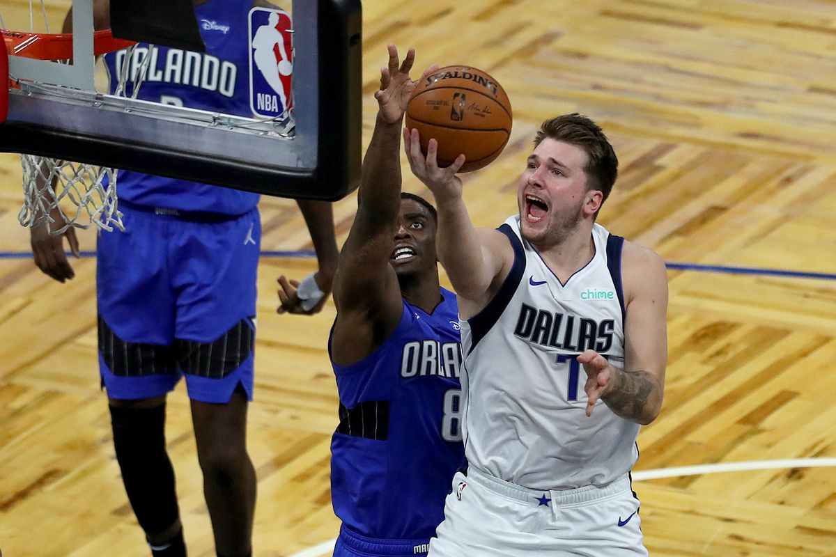 Luka Doncic of the Dallas Mavericks drives to the basket against Dwayne Bacon of the Orlando Magic during the second half at Amway Center on March 1, 2021 in Orlando, Florida.