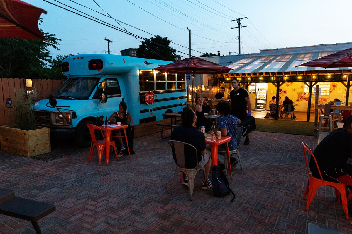 A bright blue minibus sits against the fence surrounded by tables with umbrellas and customers eating at twilight.