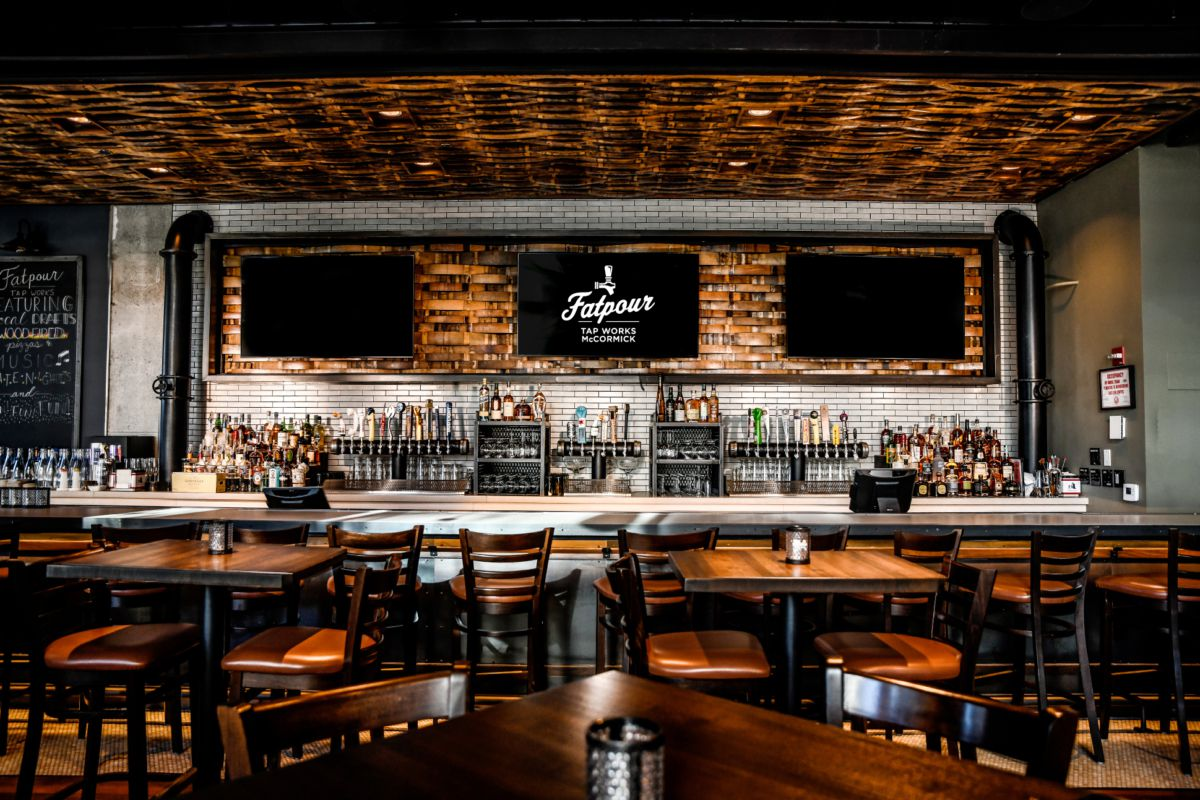 A large bar space is filled with dark wood tables and chairs. A tiled wall behind the bar offsets bottles, taps, and coolers. The brown ceiling appears to be wood woven into a basket-weave texture. Three TVs hang over the bar.