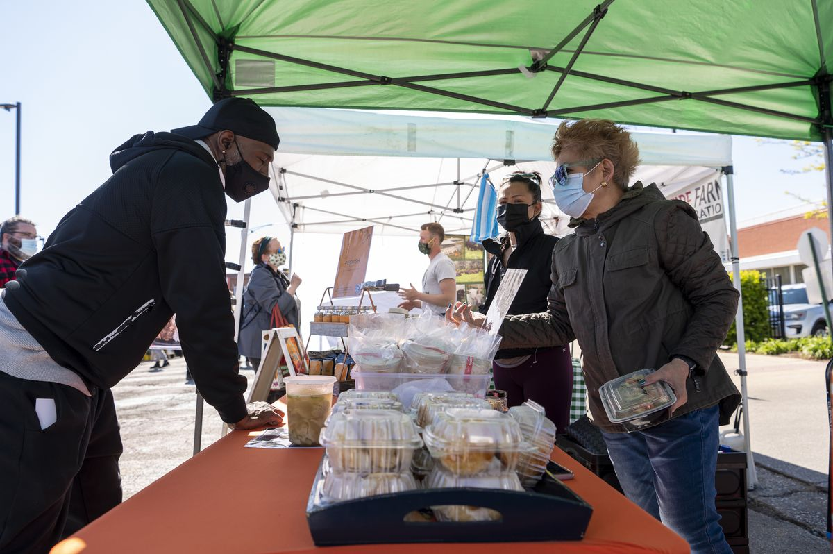 Kristine Subido, center black mask, and her mother, Melendia Subido, help a customer check out at their stall Pecking Order at the Andersonville Farmers Market, Wednesday, May 12, 2021.