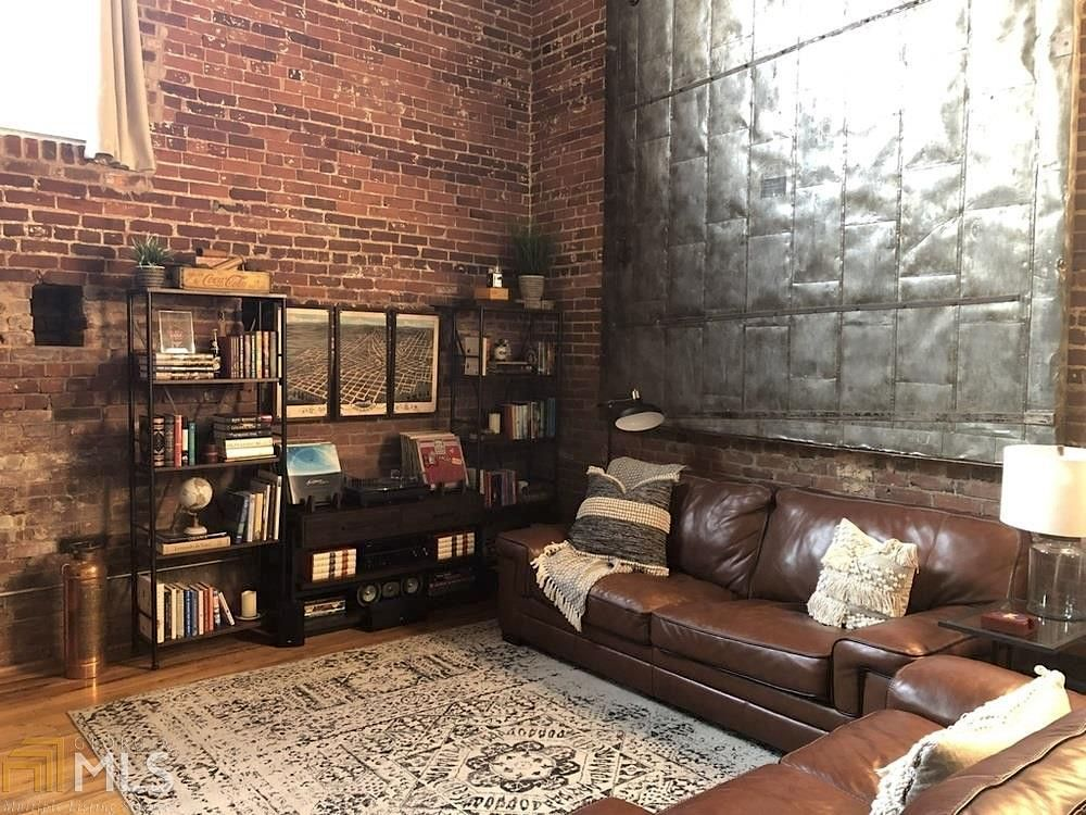 A large living room with brick walls and leather couches.