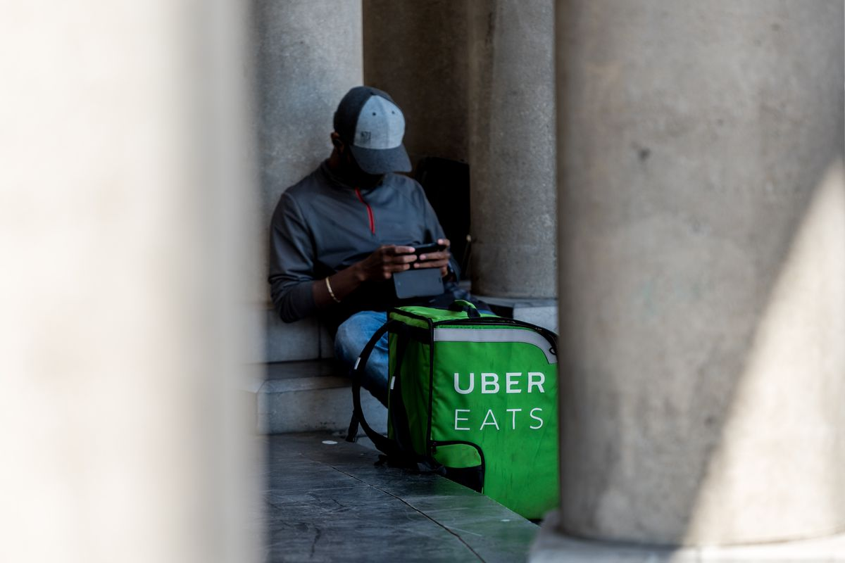 Man rests in between two columns, with a Uber Eats delivery bag sitting alongside him.