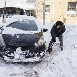 A person shovels out a car Tuesday near Southport Avenue and Eddy Street in Lake View.