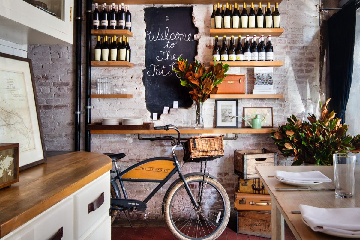 The interior of a restaurant that showcases a bicycle parked against a wall with a blackboard on it