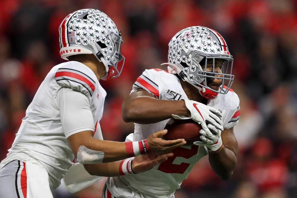Ohio State Buckeyes quarterback Justin Fields hands the ball to running back J.K. Dobbins against the Wisconsin Badgers during the first half in the 2019 Big Ten Championship Game at Lucas Oil Stadium.