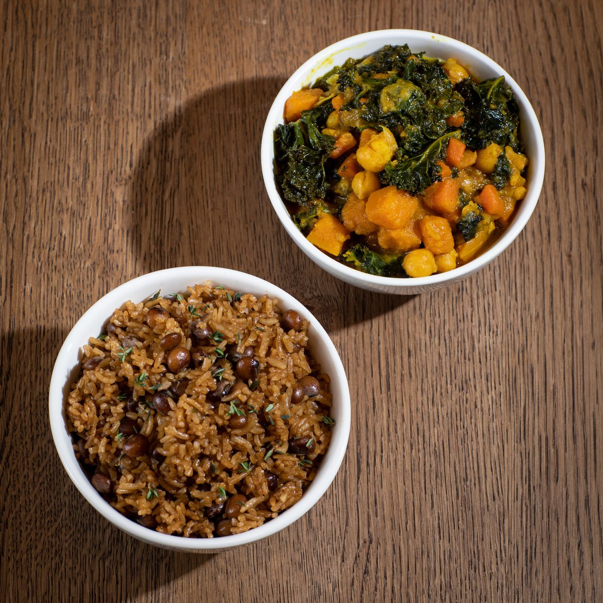 Two white bowls, one filled with brown rice and peas and the other filled with orange squash cubes and green kale, set on a wooden table