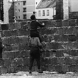 A boy sitting on the shoulders of another child peers at the Liesen Street in Wedding, West Berlin, on August 23, 1961, over the wall towards the eastern part of the city.