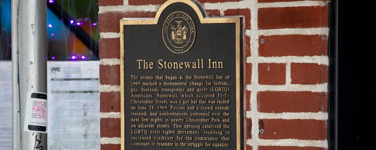 A black and gold sign on a brick wall denotes the Stonewall Inn in New York City as a New York State Historic Site.