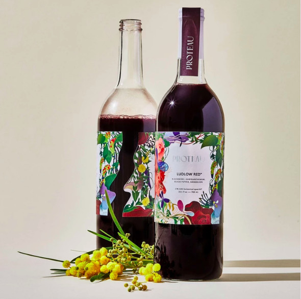 Two bottles that look like red wine, with flower-filled labels
