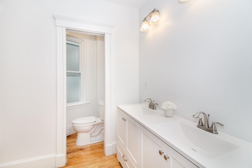 A bathroom with a long counter with two sinks and a cubbyhole for the toilet.