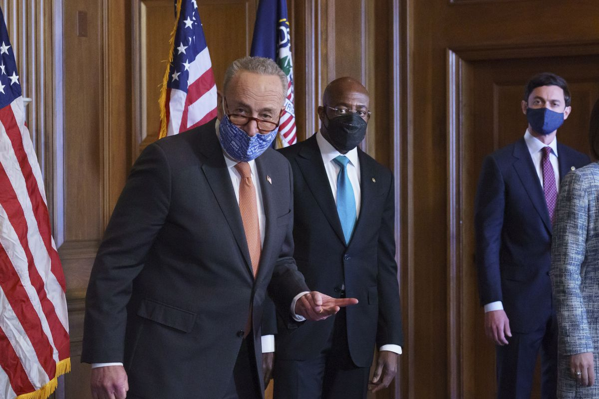 On the first full day of the Democratic majority in the Senate, Majority Leader Chuck Schumer, D-N.Y., left, is joined by Sen. Raphael Warnock, D-Ga., center, and Sen. Jon Ossoff, D-Ga., during a press event at the Capitol in Washington, Thursday, Jan. 21, 2021.