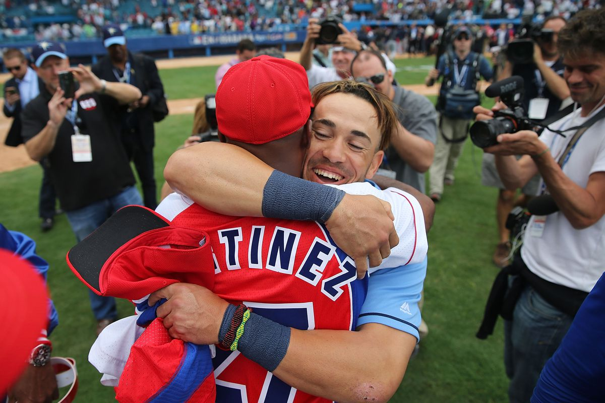 Tampa Bay Rays, Dayron Varona, who defected from Cuba in 2013, is hugged by members of the Cuban National team after an exposition game at the Estado Latinoamericano March 22, 2016 in Havana, Cuba.