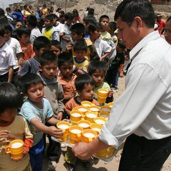 A worker with the Johannes Gutenberg Cultural Association passes out mugs of oatmeal to impoverished children in Lima, Peru. The Church provides assistance to the association with donations of food, missionary service and professional expertise. More than 11,000 children receive a hot breakfast each weekday thanks to the humanitarian program.